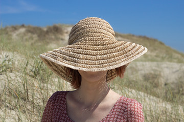 woman with empowered personality of short hair in dark brown color wearing sun hat fashion sitting on the beach in sunny day and blue sky relaxing and enjoying summer