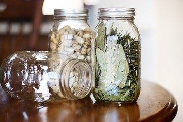 Mason jars with pistachios and bay leaves against bright background