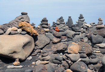 beautiful towers of stacked pebbles and stones in a large arrangement on a black sand beach with blue sky