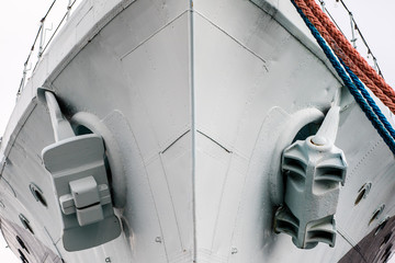 The anchor of a large warship standing in the port. Bow of a ship with an anchor on the side.