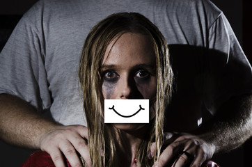 concept abused woman with gauged mouth and a fake smile hiding the abuse and a man standing behind her with his hands on her shoulders