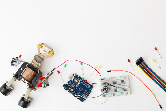 A metal robot and an electronic board that can be programmed. Robotics and electronics. A robot assembly builder. Laboratory in the school. Mathematics, engineering, science.