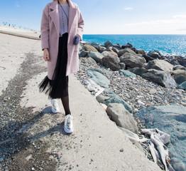 A girl is walking on the beach near the sea