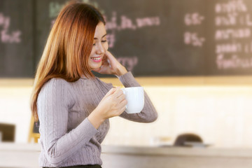 Smiling woman with a cup of coffee in her hands sits in a modern cafe.