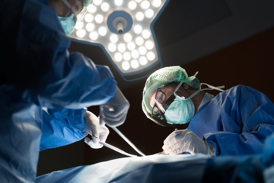 Asian doctor and an assistant in the operating room for surgical venous vascular surgery clinic in hospital.