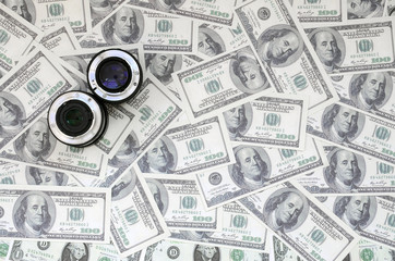 Two photographic lenses lie on the background of a lot of dollar bills. Space for text