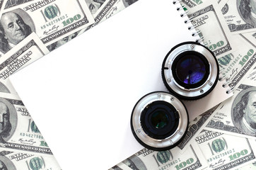 Two photographic lenses and white notebook lie on the background of a lot of dollar bills. Space for text