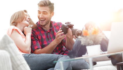 modern young couple laughing and discussing the photos on the camera