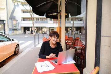 lady sitting in outdoor cafe and have conversation  with sister via laptop. Sisters not communicate for long time and woman very happy. Female smiling  waving,  blows air kiss and showing hea