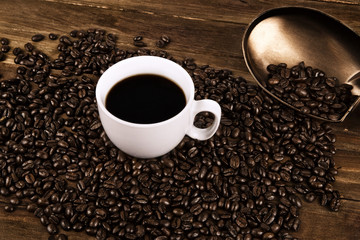 Cup of coffee and coffee beans on old wooden background.