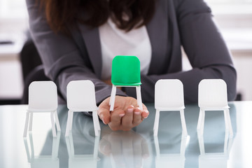 Businesswoman Choosing Green Chair Among White Chairs In A Row