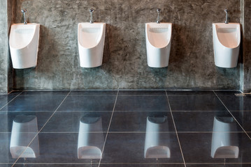 Row of white ceramic urinals for men in public toilet bathroom on the concrete wall