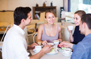 group of four young friends enjoying coffee at pastry bar