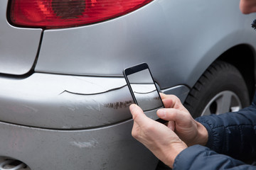 Person Taking Photo Of Damaged Car Through Smartphone