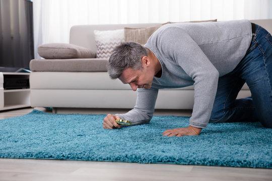 Man Looking At Carpet Through Magnifying Glass