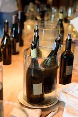 Wine bottle immersed in an ice bucket.