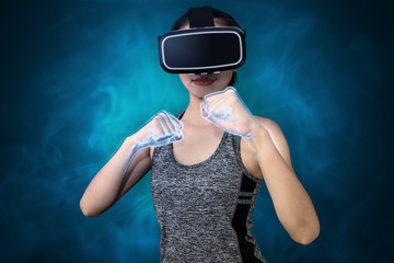 Young sport woman using VR goggle headset to play VR sport fighting game. e-Sport concept
