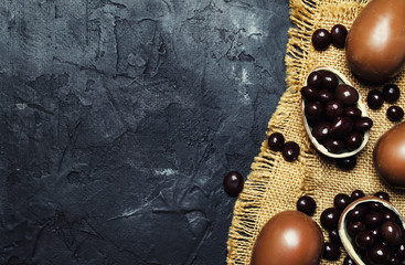 Easter composition with chocolate eggs and sweets, dark background, top view