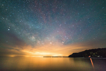 Milky Way and stars over the lake showing shoreline and cliffs at night