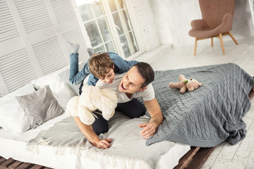 Our day off. Attractive inspired dark-haired daddy laughing and lying on the bed with his son and they having fun