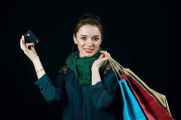 Image of a young woman with bags and credit card . Purchases by credit card