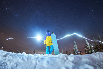 Lady snowboarder night photo against night mountains