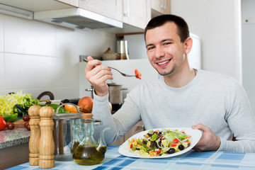 Cheerful  handsome man holding plate with salad