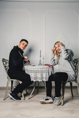 A young couple dining at the table in the room and have fun