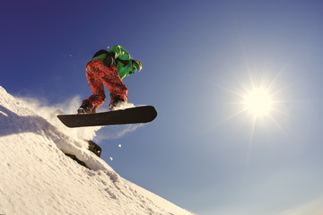 The snowboarder jumps from the springboard against the blue sky in the backlight.