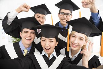 happy graduates making selfie photo in classroom.