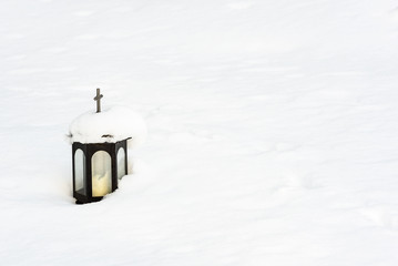 Small black lantern on a snow covered cemetery.