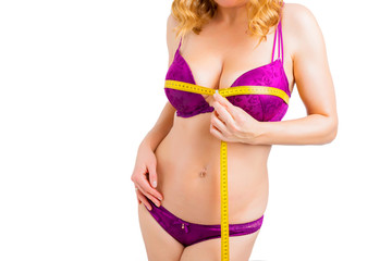 Woman measuring her bust with measurement tape