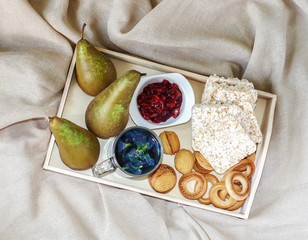 Breakfast in bed in a wooden tray with pears, pear jam, bisquits, sweet cookies, teapot and cup of organic blue thailand tea anchan, clitoria, butterfly pea.