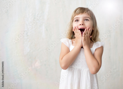 0bd6d96bf Portrait of pretty little girl in white dress holding her hands on ...