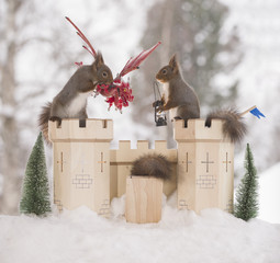 red squirrels with castle and dragon  in a winter