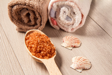Wooden spoon with brown sea salt for bathroom procedures with towels on the background