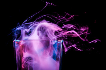 Close-up glass transparent glass for beer filled with a wig from blue, blue, violet smoke smokes and stands on a black isolated background.