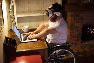 Disabled man in virtual reality headset using laptop