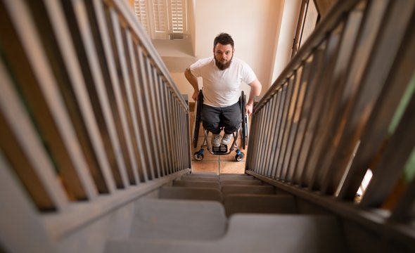 Disabled man in wheelchair looking at stairs