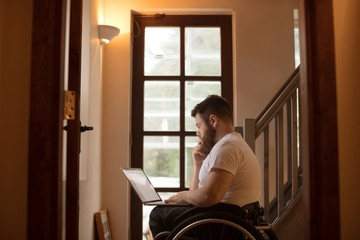 Disabled man using laptop at home