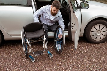 Disabled man holding wheelchair while boarding in his car