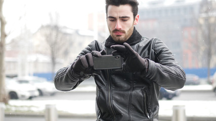 Handsome trendy man wearing black leather jacket using cell phone to take photos, outdoor in city setting in winter day shot