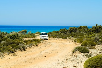 Car driving on a stony path in front of the ocean on Kos island