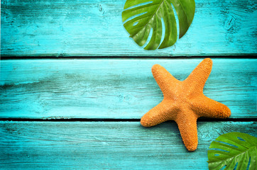 Summer sea background. Starfish on blue wooden background