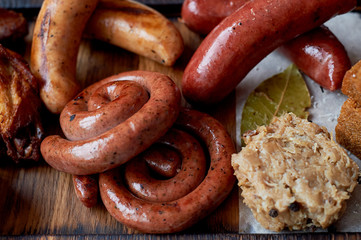 German hearty lunch in the pub. Grilled sausages, stewed cabbage, croutons, sauce. Beer snack