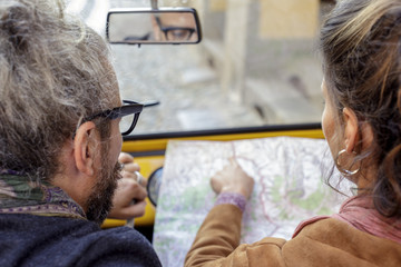 Woman and man talking looking at map. Back view. Caucasian couple in love roadtrip vacation italian travel on convertible car