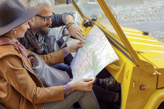 Woman and man talking looking at map. Caucasian couple in love roadtrip vacation italian travel on convertible car