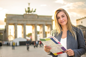 Portrait of smiling young woman with map near Brandenburg Gate in Berlin, Germany.