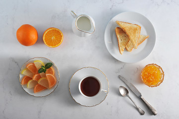 Table setting for breakfast. In the frame orange jam, toast, tea, milk in the milkman, marmalade in the form of orange slices, oranges, cutlery. Light background. Close-up. View from above.