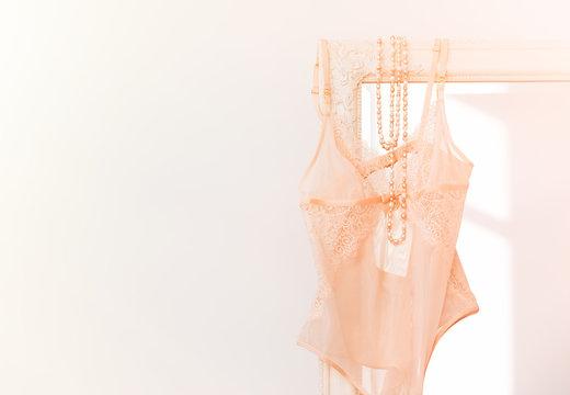 Beige sexy woman's bodysuit lingerie hanging on mirror